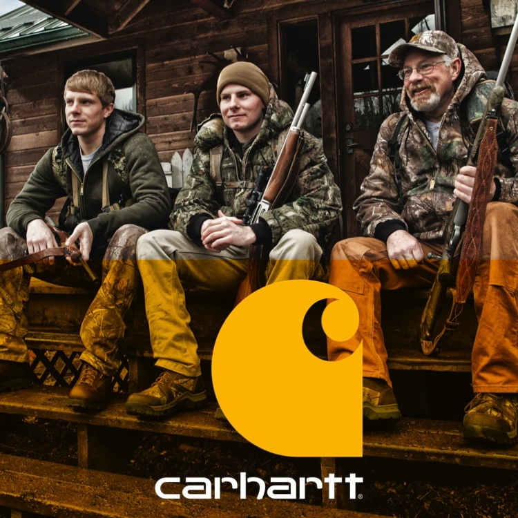 Three hunters sitting in Carhartt clothing on front porch with Carhartt logo