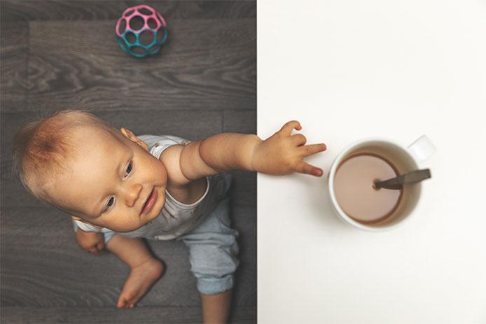 Baby reaching for mug
